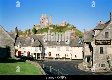 Corfe castle ruins rise above the Greyhound pub in the ancient village of Corfe Castle, Dorset, England - Stock Photo