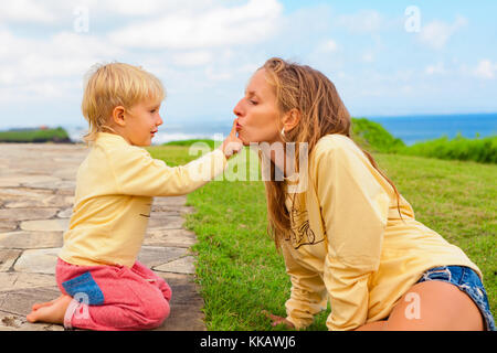Happy family on outside walk. Child sitting on green grass lawn have fun. Young attractive mother kiss son finger. - Stock Photo