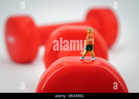 Sport and fitness concept. Man runner miniature figure running on red 1kg dumbbell - Stock Photo