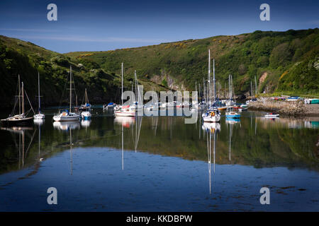 Solva harbour, Pembrokeshire, Wales, UK with small boats at anchor and reflections in the perfectly still water - Stock Photo