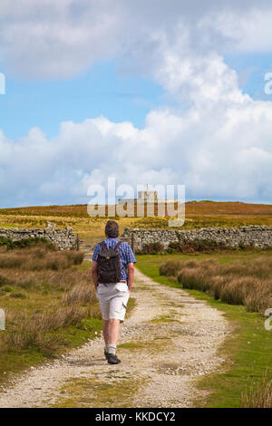 Man walking along pathway towards Tibbetts, formerly Admiralty Lookout post, at Lundy Island, Devon, England UK - Stock Photo