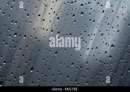 close-up of diagonal bands of raindrops on a fogged window - Stock Photo
