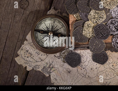 Old brass compass with gold and silver coins and treasure map - Stock Photo