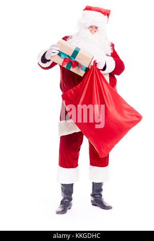 Putting Christmas gift into sack - Stock Photo