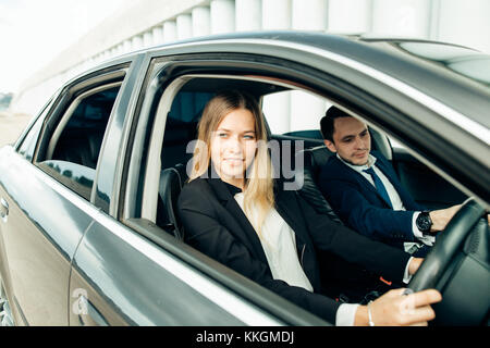 Driving instructor and woman student in examination car. - Stock Photo