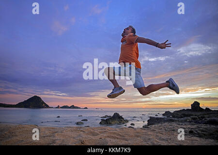 Happy Western tourist jumping in the air at sunset on the Kuta beach on the island Lombok, Lesser Sunda Islands, - Stock Photo
