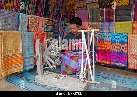 Indonesian weaver weaving traditional songket fabrics on primitive wooden loom in the Sasak village Sade on the - Stock Photo