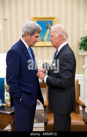 Vice President Joe Biden talks with Secretary of State John Kerry in the Oval Office, Oct. 1, 2014. - Stock Photo