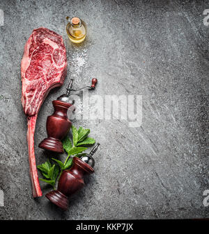 Raw tomahawk beef steak , preparation for grill or cooking on dark rustic concrete background, top view, place for - Stock Photo