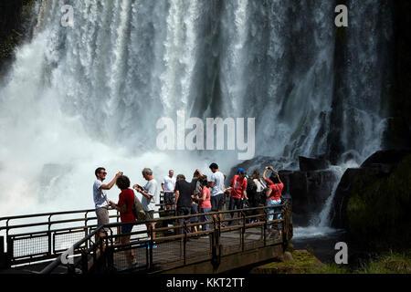 Tourists on lookout by Iguazu Falls, on Argentina - Brazil Border, South America - Stock Photo