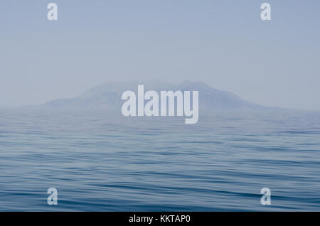 A rocky islet appears over the Mediterranean sea in a mist near Bozcaada Island, Turkey. - Stock Photo