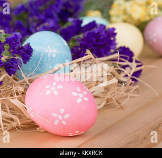 Decorated Easter eggs among flowers on a wood surface - Stock Photo