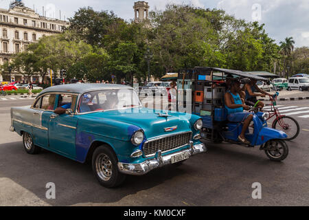 An old classical car, a large motorbike (carrying crates) and a pair of three wheeler bicycles leave the Prado and - Stock Photo