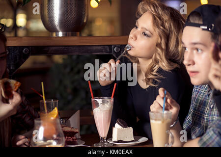 friends having a coffee together. women and man at cafe, talking, laughing - Stock Photo