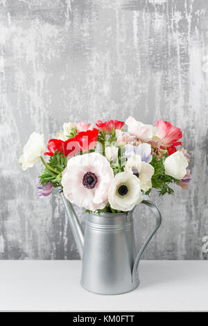 Winter flowers. Anemones in a vase watering can standing on a wooden table. On the background old gray wall art. - Stock Photo
