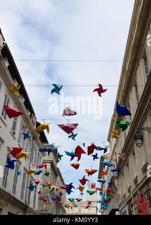 The entire display of decorative plastic pinwheels in multiple colors suspended from wires between buildings along - Stock Photo