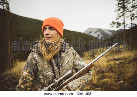 Portrait female hunter in camouflage and orange beanie holding hunting rifle in field - Stock Photo