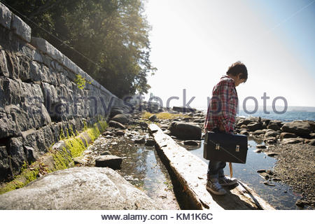 Boy with fishing tackle box standing on fallen log above ocean tidal pool - Stock Photo
