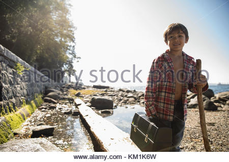 Portrait smiling boy with walking stick and fishing tackle box on sunny beach - Stock Photo