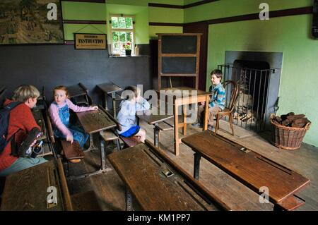 Bunratty Folk Park, Bunratty Castle, Co. Clare, Ireland. Children pupils and mother teacher explore the School House - Stock Photo
