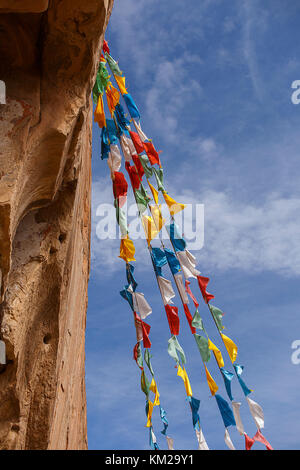 Buddhist prayer flags on the facade of the Matisi temple in China. - Stock Photo