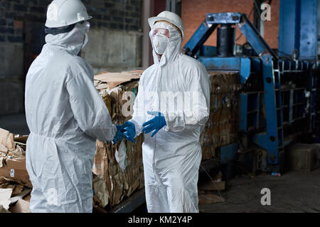 Workers in Hazmat Suits Communicating at Factory - Stock Photo
