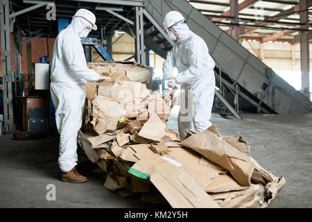 Workers in Hazmat Suits Sorting Cardboard at Modern Factory - Stock Photo