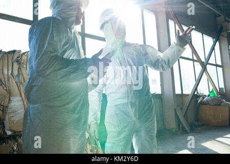Workers in Sunlight at Modern Waste Processing Plant - Stock Photo