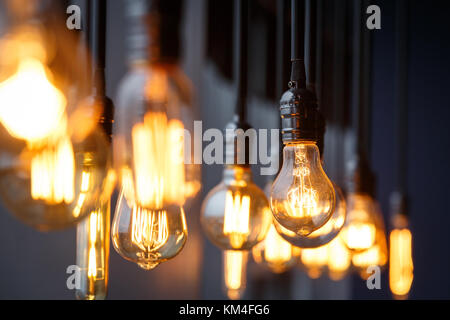 Vintage tungsten filament multiple lamps of different size and style hanging from the ceiling on a black wires as - Stock Photo
