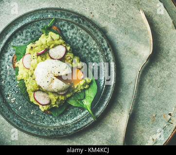 Healthy vegetarian breakfast flat-lay. Wholegrain toast with avocado, spinach, radish and poached egg on grey plate - Stock Photo