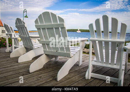 Coastal Living Lifestyle. White Adirondack chairs on a wooden waterfront deck with a waterfront view and lighthouse. - Stock Photo