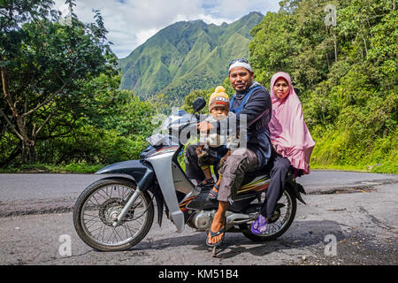 Indonesian family with toddler riding motorcycle through tropical rain forest on the slopes of Mount Rinjani, volcano - Stock Photo