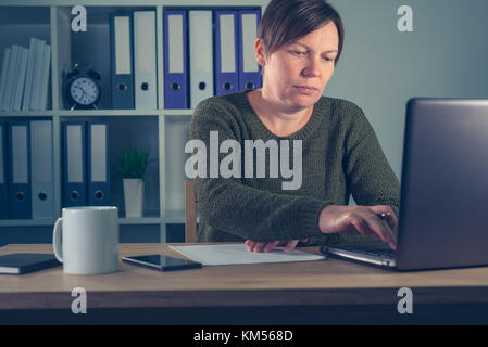 Female freelancer working overtime in home office, doing paperwork and accounting, writing notes and calculating - Stock Photo