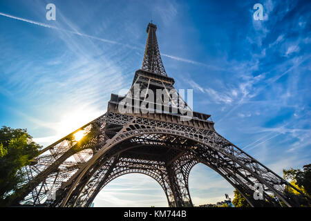 A view of the Eiffel Tower with a wide angle lens looking up from the base on a sunny afternoon - Stock Photo