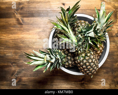 Ripe pineapple in a large bowl. On a wooden table. - Stock Photo