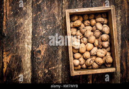 Walnuts in the box. On wooden background. - Stock Photo