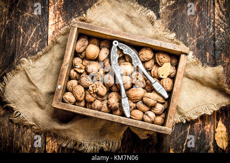 Walnuts in the box with the Nutcracker. On wooden background. - Stock Photo