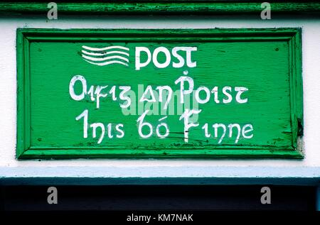 Post office sign in Irish Gaelic language hand painted on island of Inishbofin off the coast of County Galway in - Stock Photo