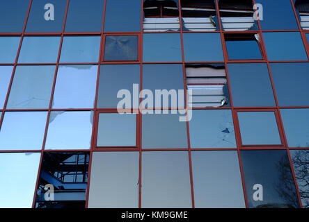 broken glass wall of a derelict modern office building - Stock Photo
