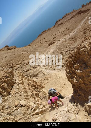 mother and child going uphill a mountain with the sea on the background - Stock Photo