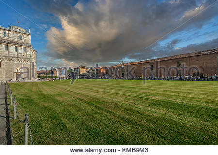 The piazza del duomo, square of Miracles in Pisa Italy with dark clouds as tourists gather in front of the cathedral - Stock Photo