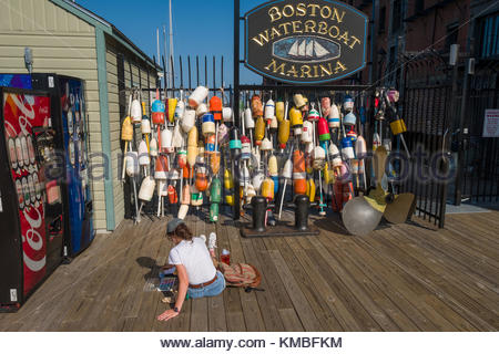 Woman sitting on wooden pier painting watercolor of wall of colorful buoys at the Boston Waterboat Marina, Boston, - Stock Photo