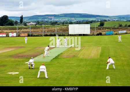 Fox Club Cricket Club playing on their club pitch at Ballymagorry, County Tyrone, Northern Ireland. Donegal hills - Stock Photo