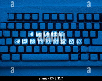 PC computer keyboard with text merry christmas on buttons covered with snow illuminated by blue neon light - Stock Photo