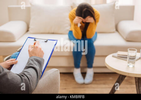 Male psychologist taking notes about upset woman problem  - Stock Photo