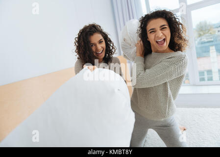Full of energy friends fighting with pillows - Stock Photo
