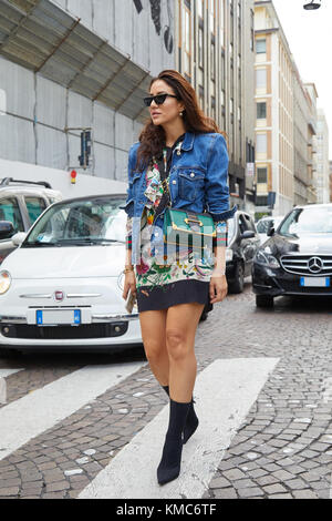 MILAN - SEPTEMBER 23: Woman with green Prada bag, floral dress and blue jeans jacket before Antonio Marras fashion - Stock Photo