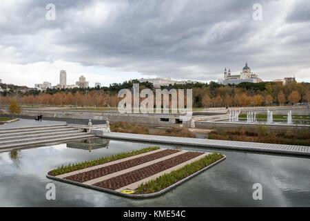 Skyline of Madrid (Spain) viewed from Segovia Bridge, including Manzanares river and Madrid Rio park. - Stock Photo