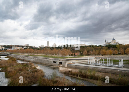 Skyline of Madrid (Spain) viewed from Segovia Bridge, including Manzanares river and Madrid Rio park. - Stock Photo
