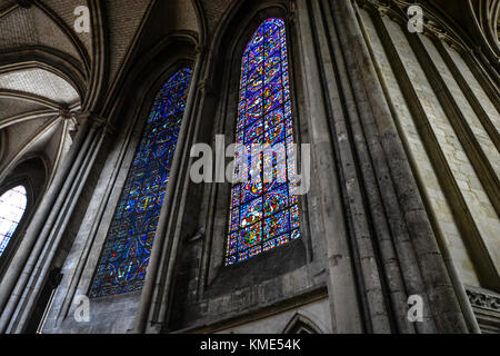 Two tall, arched stained glass windows in the interior of the Roeun Cathedral in Normandy France - Stock Photo